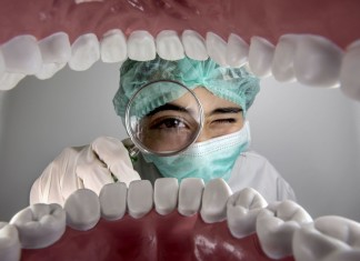 dentista com lupa na boca do paciente