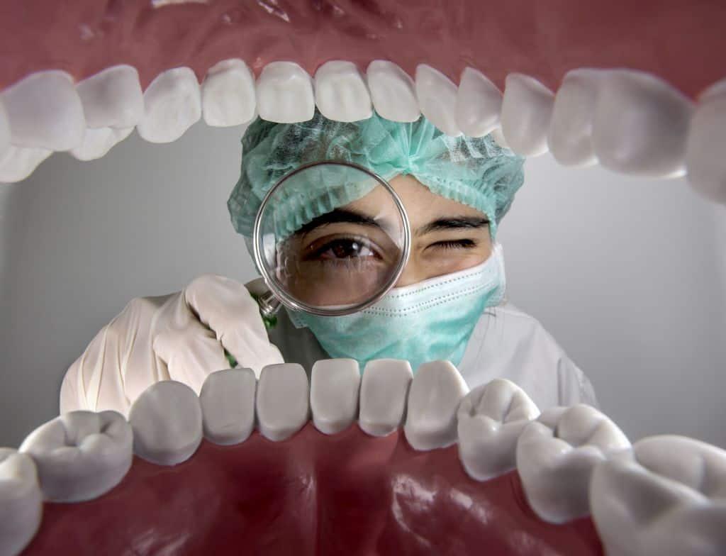 dentista com lupa na boca do paciente