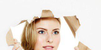 mulher olhando através de um buraco na parede